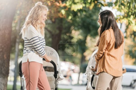 side view of smiling mothers looking at each other while walking with baby strollers in park