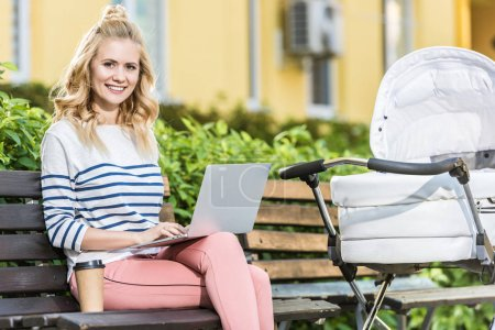 Photo for Smiling freelancer sitting with laptop on bench near baby stroller in park and looking at camera - Royalty Free Image
