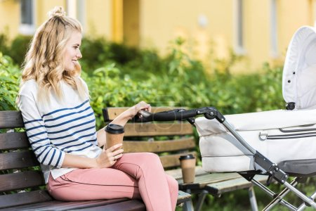 side view of smiling mother sitting on bench with coffee to go and holding baby stroller in park
