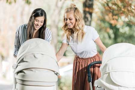 smiling attractive mothers looking in baby carriage in park