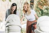 souriant séduisantes mères à la recherche en poussette dans le parc