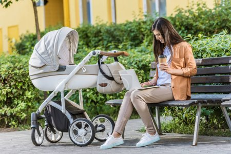 Photo for Freelancer working with laptop on bench near baby stroller in park and holding coffee in paper cup - Royalty Free Image