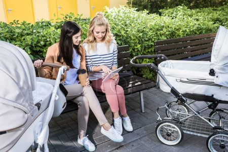 Photo for Mothers sitting on bench near baby strollers with coffee to go and looking at tablet - Royalty Free Image