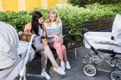 mothers sitting on bench near baby strollers with coffee to go and looking at tablet