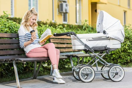 smiling mother reading book and holding coffee to go on bench near baby stroller in park