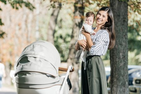 Photo for Smiling mother holding baby near stroller in park and looking at camera - Royalty Free Image