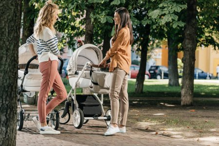 Photo for Side view of mothers talking and standing with baby strollers in park - Royalty Free Image