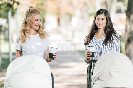 Photo for Smiling mothers standing with baby strollers and coffee in paper cups in park - Royalty Free Image