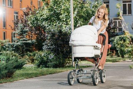 belle mère marche avec la poussette de bébé sur la rue