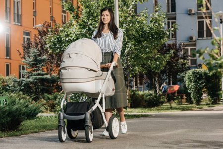 beautiful brunette mother walking with baby stroller on street