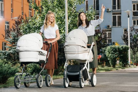 mothers walking with baby strollers on street, woman pointing on something to friend