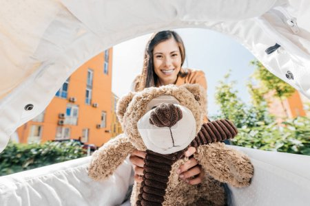 smiling mother holding teddy bear in baby stroller