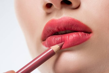 cropped view of woman applying lip pencil,  isolated on white