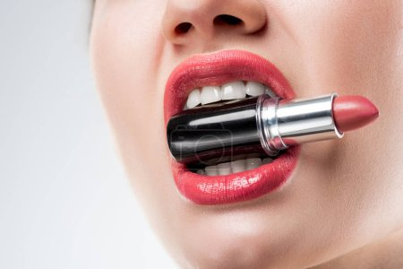 cropped view of woman holding pink lipstick in teeth,  isolated on white