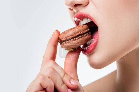 cropped view of woman biting chocolate french macaroon, isolated on white