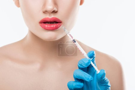 cropped view of woman making beauty injection in lips, isolated on white