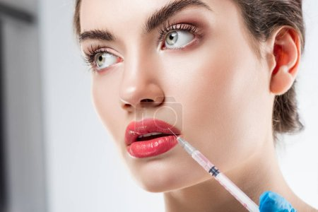 beautiful woman making beauty injection in lips