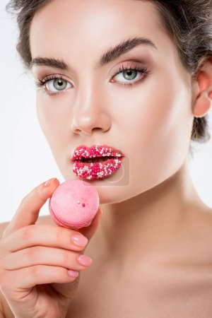 attractive woman with sugar sprinkles on lips holding pink macaron, isolated on white