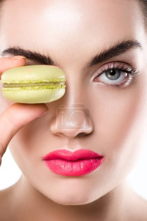 attractive woman holding sweet green macaron, isolated on white