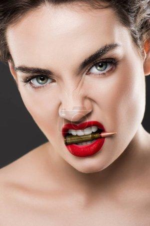 Photo pour Jolie femme en colère, tenir la balle dans les dents, isolés sur fond gris - image libre de droit