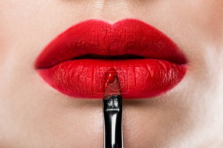 close up view of elegant woman applying red lipstick with cosmetic brush