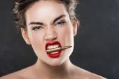 """Постер, картина, фотообои """"агрессивный элегантная женщина, держащая пуля в зубы, изолированные на серый"""""""