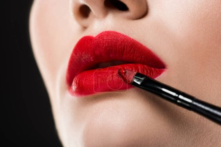 Photo pour Vue recadrée de femme appliquer le rouge à lèvres avec pinceau cosmétique, isolé sur fond gris - image libre de droit