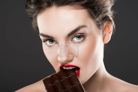 attractive woman biting chocolate bar, isolated on grey