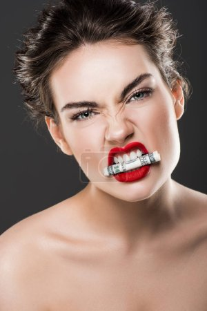 angry beautiful woman holding dollar banknote in teeth, isolated on grey