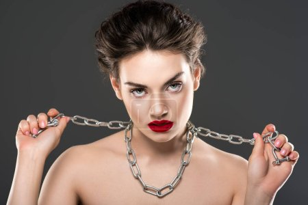 young naked woman with chain on neck, isolated on grey
