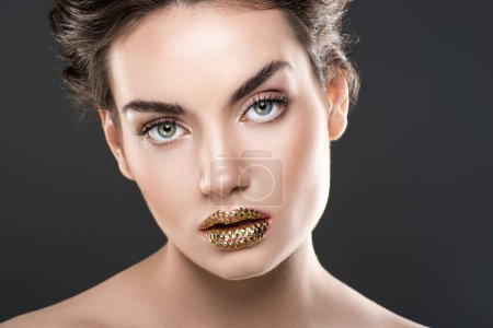 beautiful woman with golden lips, isolated on grey