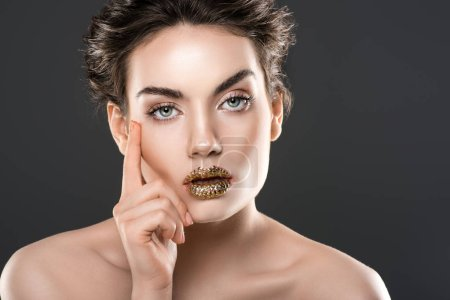 beautiful pensive woman with golden lips, isolated on grey