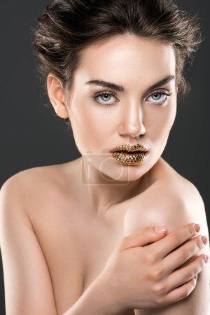 stylish nude woman with golden lips, isolated on grey