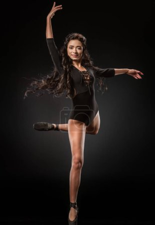 smiling ballerina in black bodysuit and ballet shoes dancing on dark backdrop