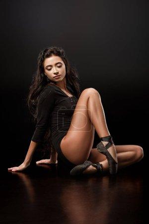beautiful ballerina in black bodysuit and ballet shoes on dark backdrop