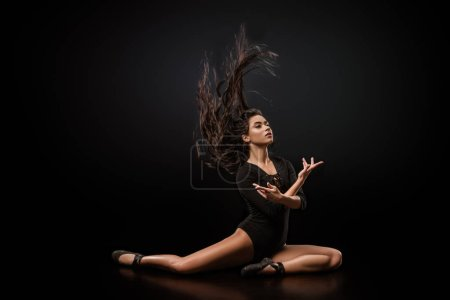 young attractive ballerina in black bodysuit and ballet shoes posing on dark backdrop