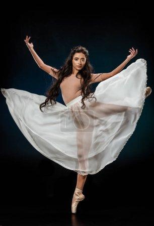 young female ballet dancer in white skirt posing on dark backdrop