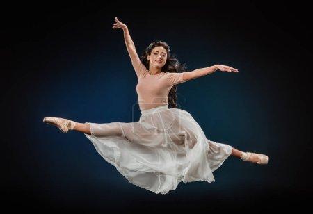 young ballerina in elegant clothing jumping on dark backdrop