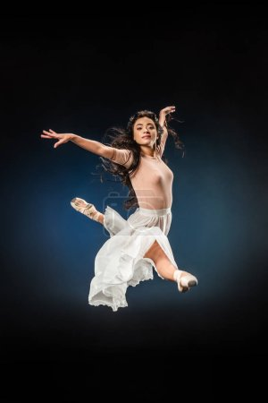 young ballerina in elegant clothing jumping on dark backdrop