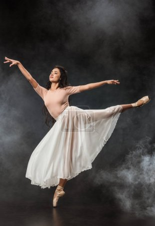 beautiful young ballerina in white skirt dancing on dark background with smoke around