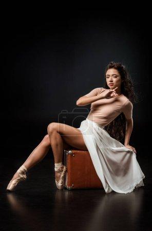 side view of attractive ballerina in white skirt on retro suitcase on dark background