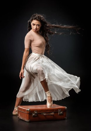 beautiful ballerina in white skirt standing with one leg on retro suitcase on dark background