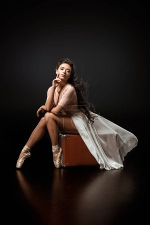 young thoughtful ballerina in white skirt sitting on retro suitcase on dark background