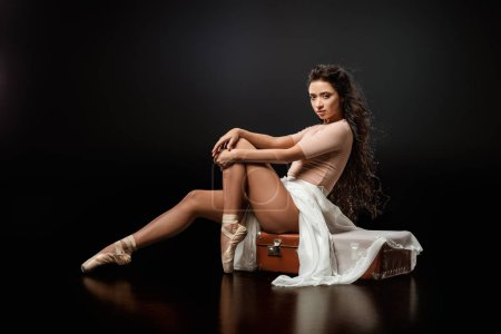 side view of beautiful ballerina in white skirt sitting on retro suitcase on dark background