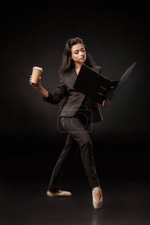 attractive businesswoman in suit and ballet shoes with folder and coffee to go posing on black backdrop