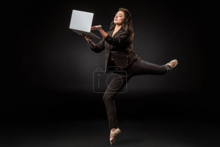 businesswoman in suit and ballet shoes using laptop on black background