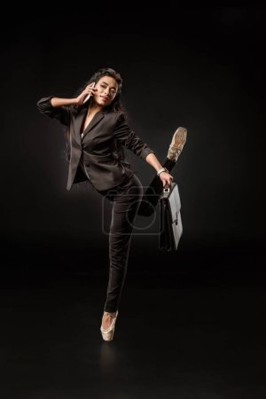 stylish businesswoman in formal wear and ballet shoes talking on smartphone on black backdrop
