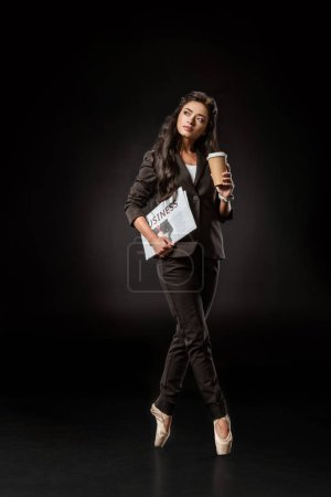 pensive businesswoman in ballet shoes with newspaper and coffee to go on black backdrop