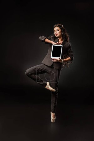 beautiful businesswoman in suit and ballet shoes showing tablet with blank screen on black backdrop