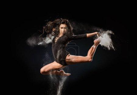 beautiful ballerina in black bodysuit with talc powder jumping on dark background
